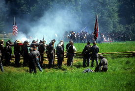 stock photo of rebs  - Confederates volley fire on advancing Union soldiers Civil War battle reenactment  - JPG