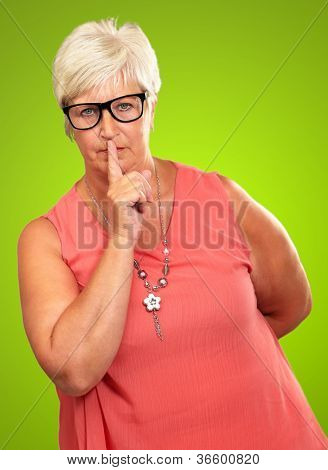 Senior Woman With Finger On Lips Isolated On Green Background