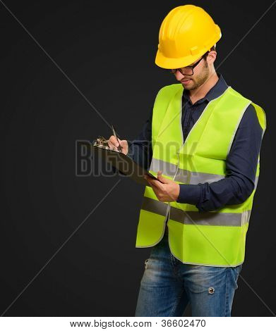 A Young Engineer Holding Writing Pad And Pen On Black Background
