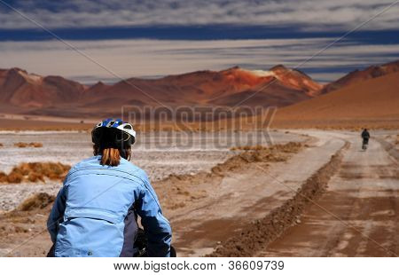 Woman cycling through the Andes