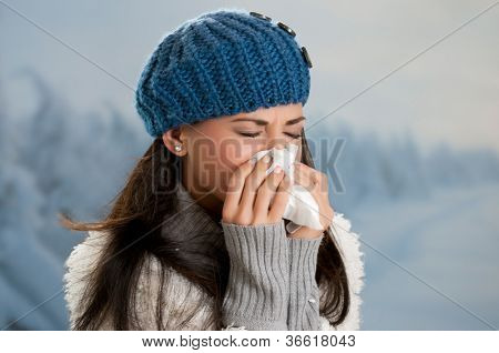 Young woman getting sick with flu in a winter day outdoor