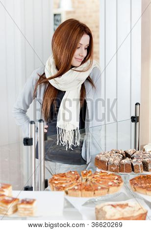 Woman in scarf looking at the bakery showcase full of different pieces of cakes