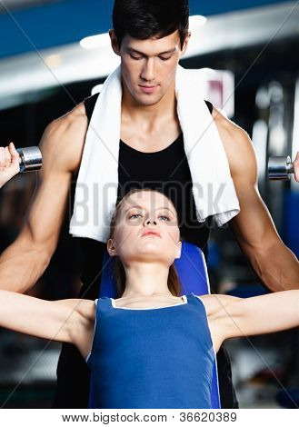 Trainer helps woman to exercise with dumbbells in fitness gym