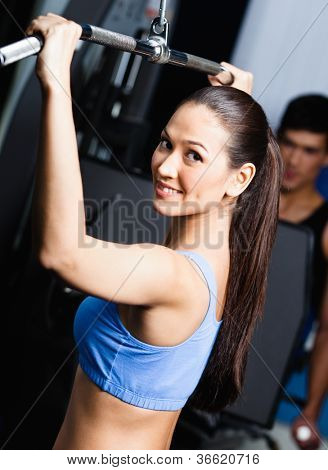 Athletic young woman works out on simulator in fitness gym