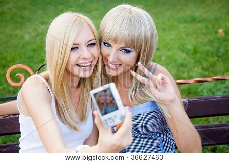 Two beautiful young girl friends with a digital photo camera