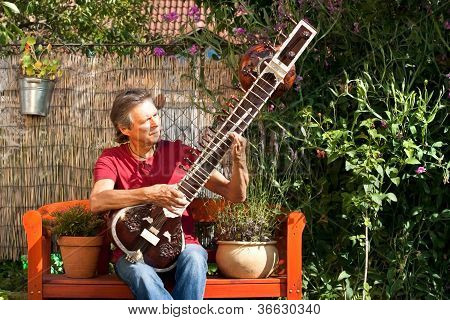 Elderly Man Sitting In His Garden And Playing A Sitar