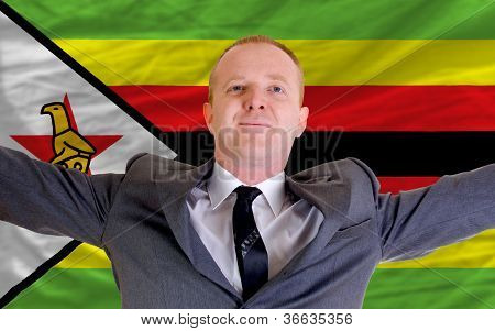 Happy Businessman Because Of Profitable Investment In Zimbabwe Standing Near Flag