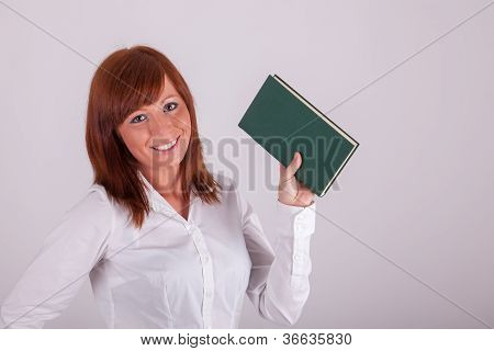 A Young Beautiful Woman Is Holding Up A Book