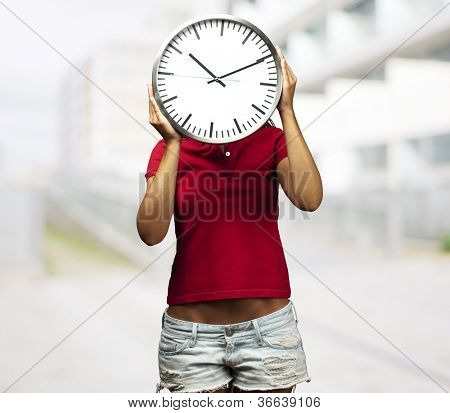 woman holding clock in front of her head