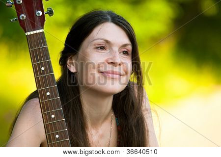 Portret young woman with guitar outdoors