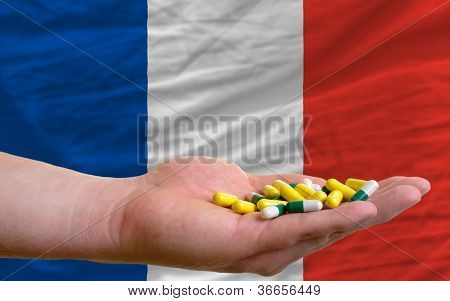 Holding Pills In Hand In Front Of France National Flag