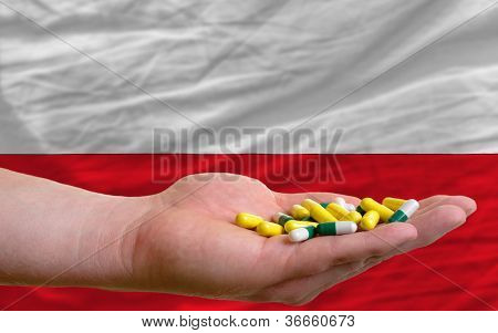 Holding Pills In Hand In Front Of Poland National Flag