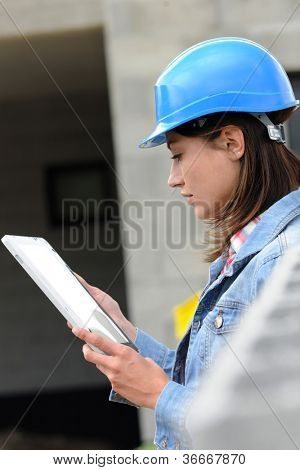 Aechitect on building site working with electronic tablet