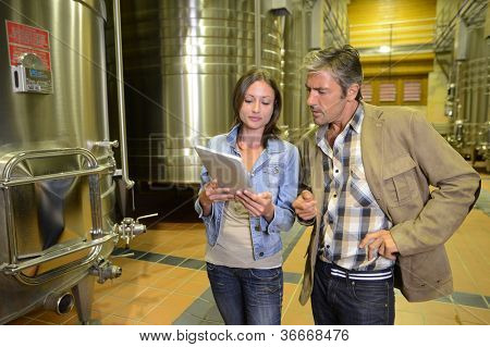 Winemaker with client in winery looking at electronic tablet