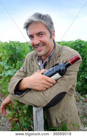 Successful winemaker in vineyard with bottle of red wine