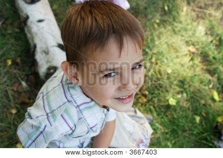 Boy Sitting On Log, Looking Up