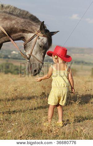 joven alimentación caballo sobre fondo natural