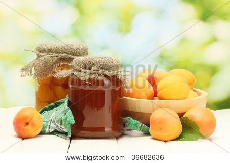 canned apricots and jam in a jars and ripe apricots in bowl on wooden table on green background