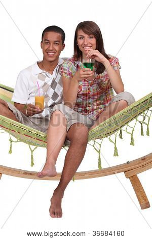 Couple sat on hammock with cocktails