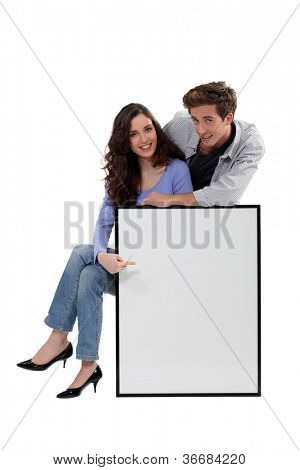 Young couple with a large picture left blank for your message