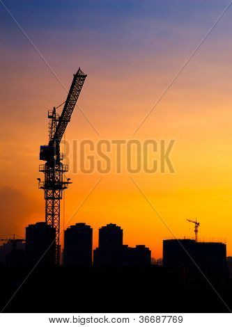 Silhouette of the tower crane at dusk on the construction site with city building background