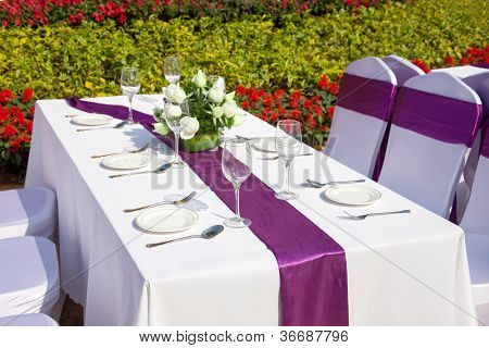 outdoor tables with served plates and wine glasses in the garden