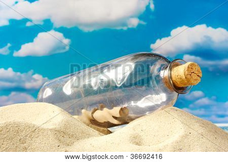 Glass bottle with note inside on sand, on blue sky background