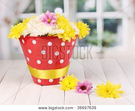 Red pail of peas with flowers on white wooden  table on window background