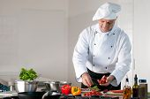 stock photo of chef cap  - Happy smiling mature chef preparing a meal with various vegetables - JPG