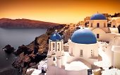 Churches on Santorini Cliffs with orange sky