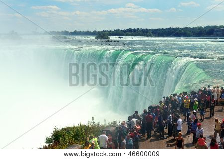 NIAGARA FALLS, NY - SEPT 1: Visitors watch Horseshoe Falls on September 1, 2012 in Niagara Falls, New York. Niagara Falls is the waterfalls with the highest flow rate in the world.