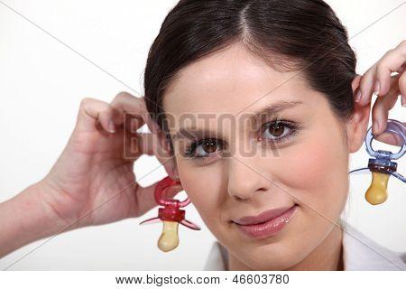 Mulher segurando chupetas de bebê perto de seus ouvidos