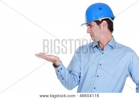 Man with a helmet disgusted by his hand