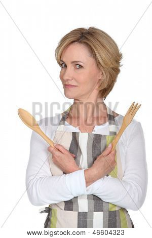 Woman wearing apron with wooden salad servers and an odd expression