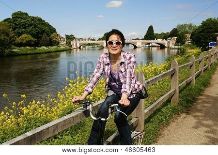 Smiling East Asian Woman With Bicycle On Sunny Day
