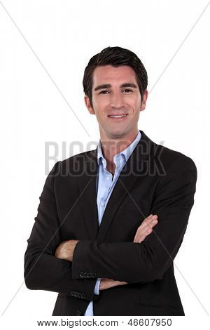 Upbeat businessman with arms folded