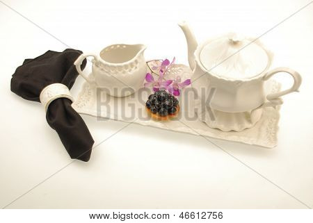 White on white china service with pastry, flowers and napkin
