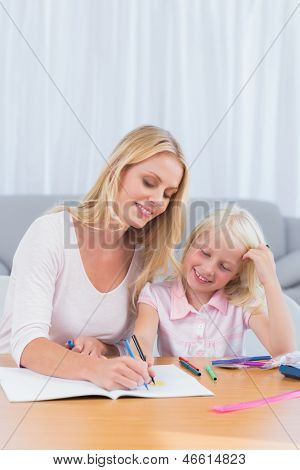 Smiling mother drawing with her daughter in the living room