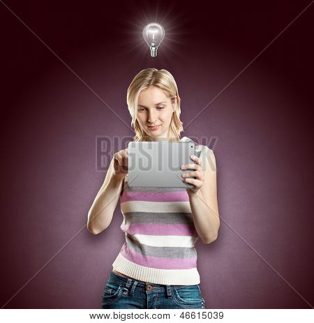Idea concept. Woman with touch pad in her hands, with lamp above her head