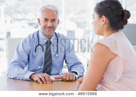 Attractive doctor sitting in front of patient in the office at desk