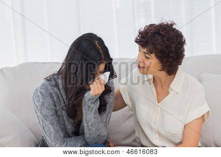 Patient crying next to her therapist while she is comforting her