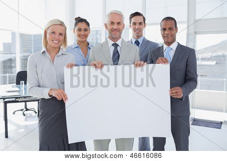 Business team holding large blank poster and smiling at camera