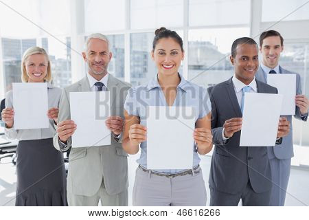 Business team showing blank pages and smiling at camera