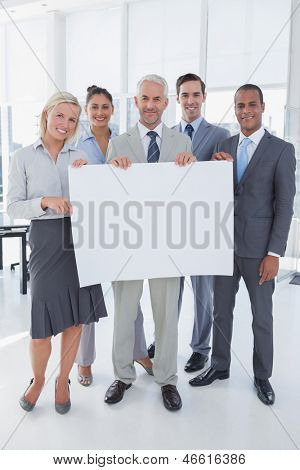 Happy business team holding large blank poster and looking at camera