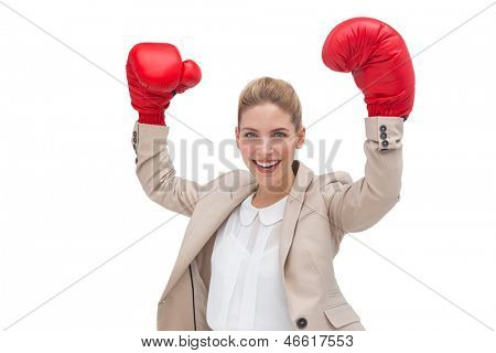 A cheering businesswoman wearing boxing gloves with arms raised