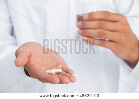 Doctor holding tablets and glass of water on white background