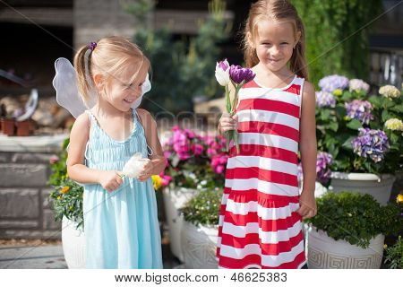 Sweet Little Girls In A Country Yard With Flowers In Their Hands