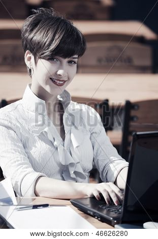 Young businesswoman with laptop at sidewalk cafe