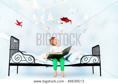 Cute little boy sitting on the bed and reading fairy tales. Dream world.
