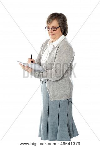 Senior Woman Writing In Spiral Notebook